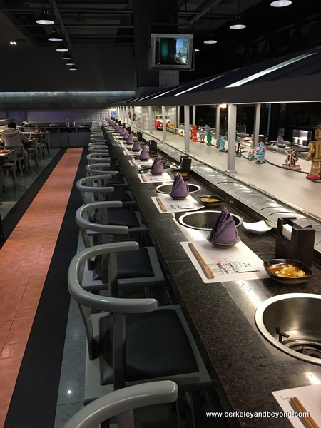 seating along conveyor belt at Huang Cheng Lao Ma hot pot restaurant in Chengdu, China