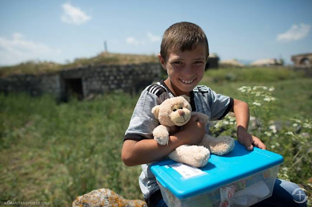 Operation Christmas Child boy with shoebox and stuffed toy