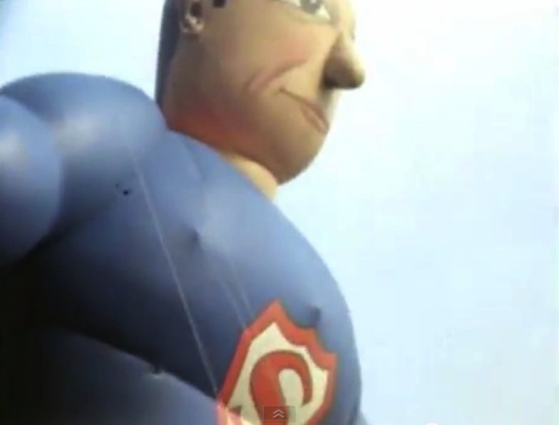 Close-up of inflated Superman balloon, with cartoonish face and vintage 'S' insignia