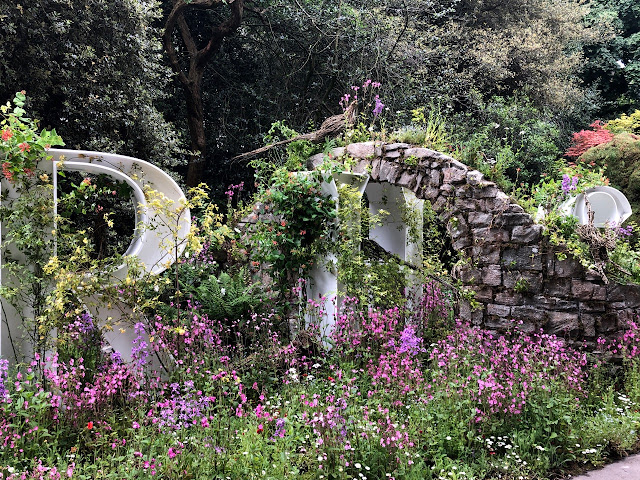 Giant letters RHS and stone arch surrounded by wild flowers