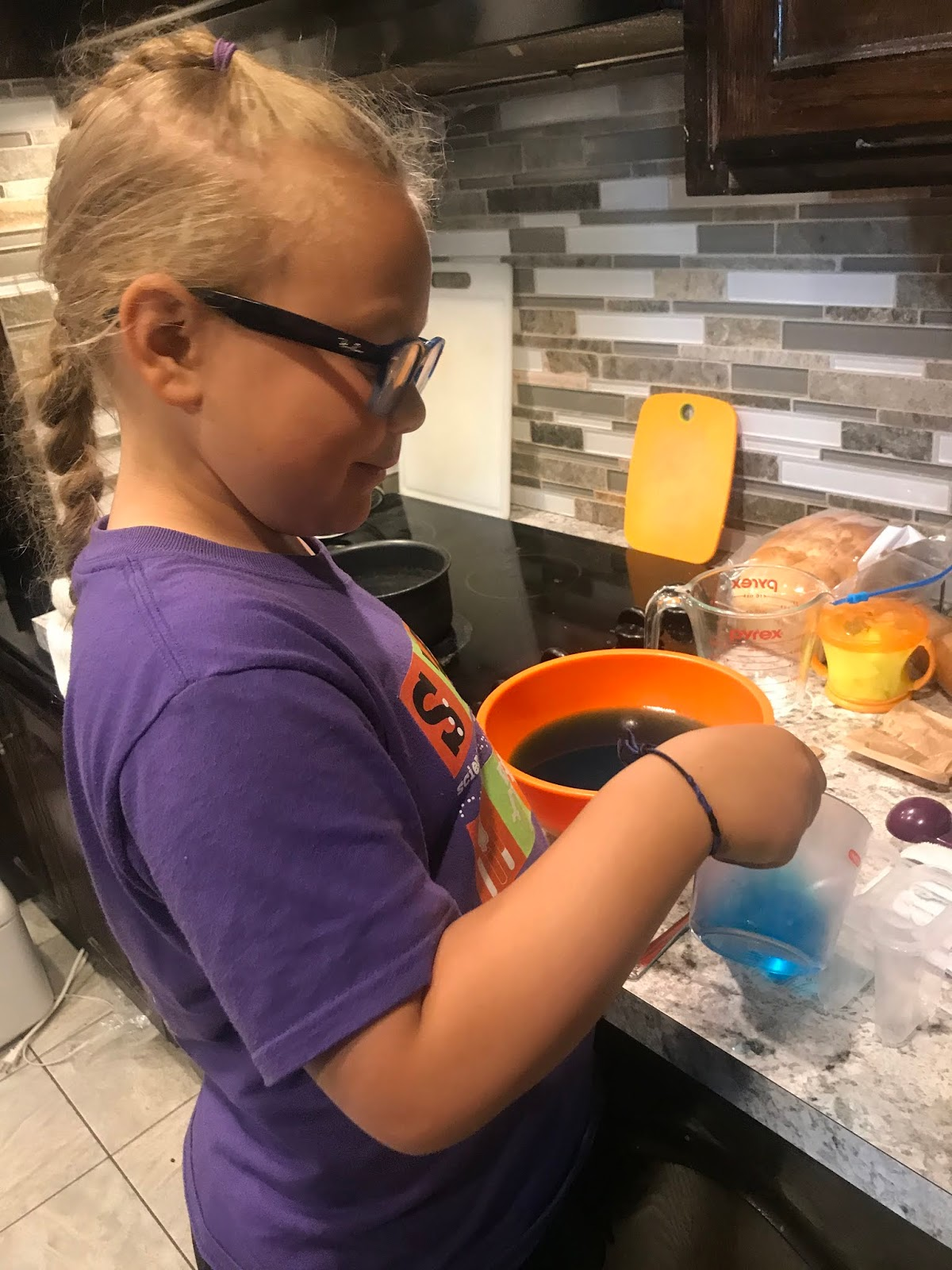 a side view of a girl pouring liquid mix into molds