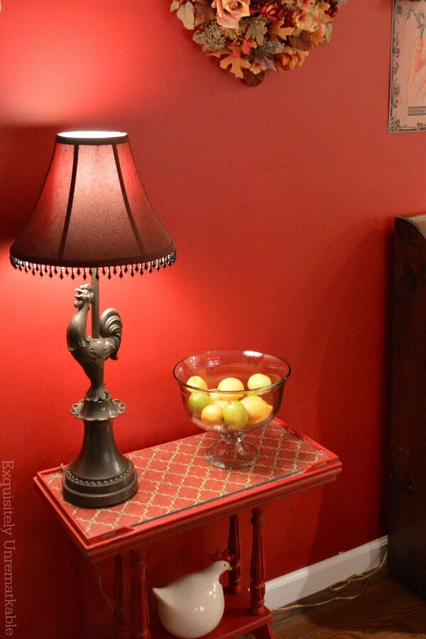Small red painted table in the hallway with rooster lamp and lemon bowl on it
