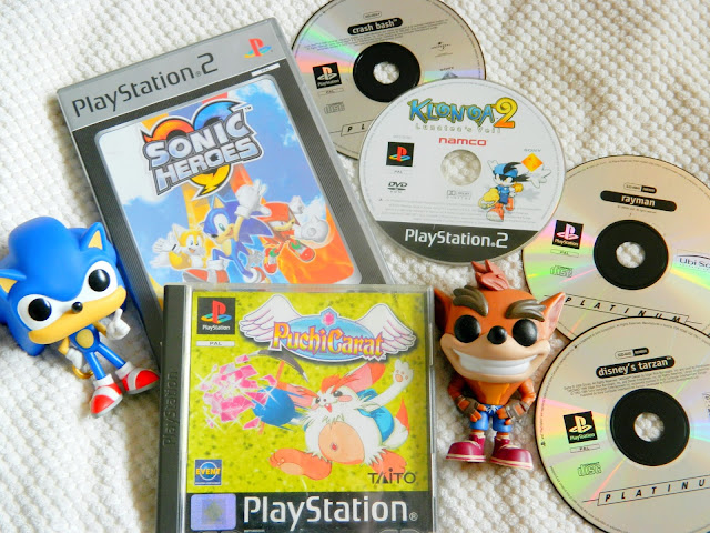 A photo showing a collection of playstation games, both discs and cased games, plus a Crash Bandicoot figure and Sonic the Hedgehog one