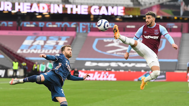 West Ham winger Said Benrahma acrobatically brings the ball under control, with Arsenal defender Calum Chambers close by