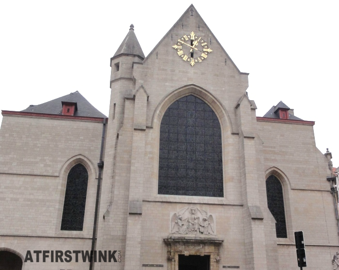 A church with a beautiful clock and angels above the entrance in Brussels