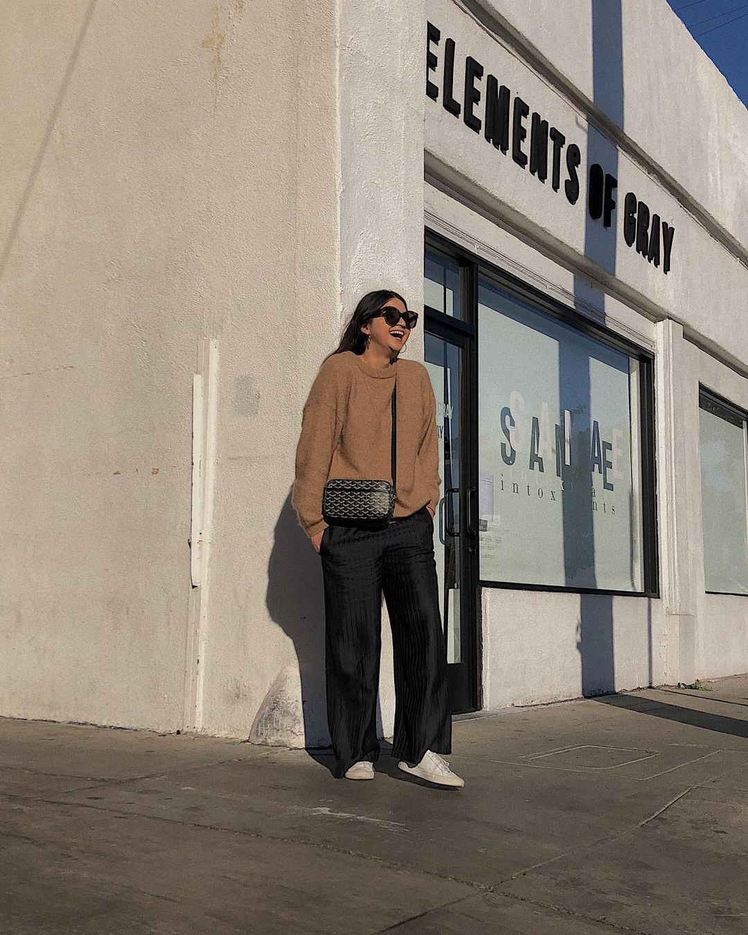 Effortless Casual Spring Outfit Idea —Annabel Ly in a camel sweater, crossbody bag, wide-leg pants, and white sneakers