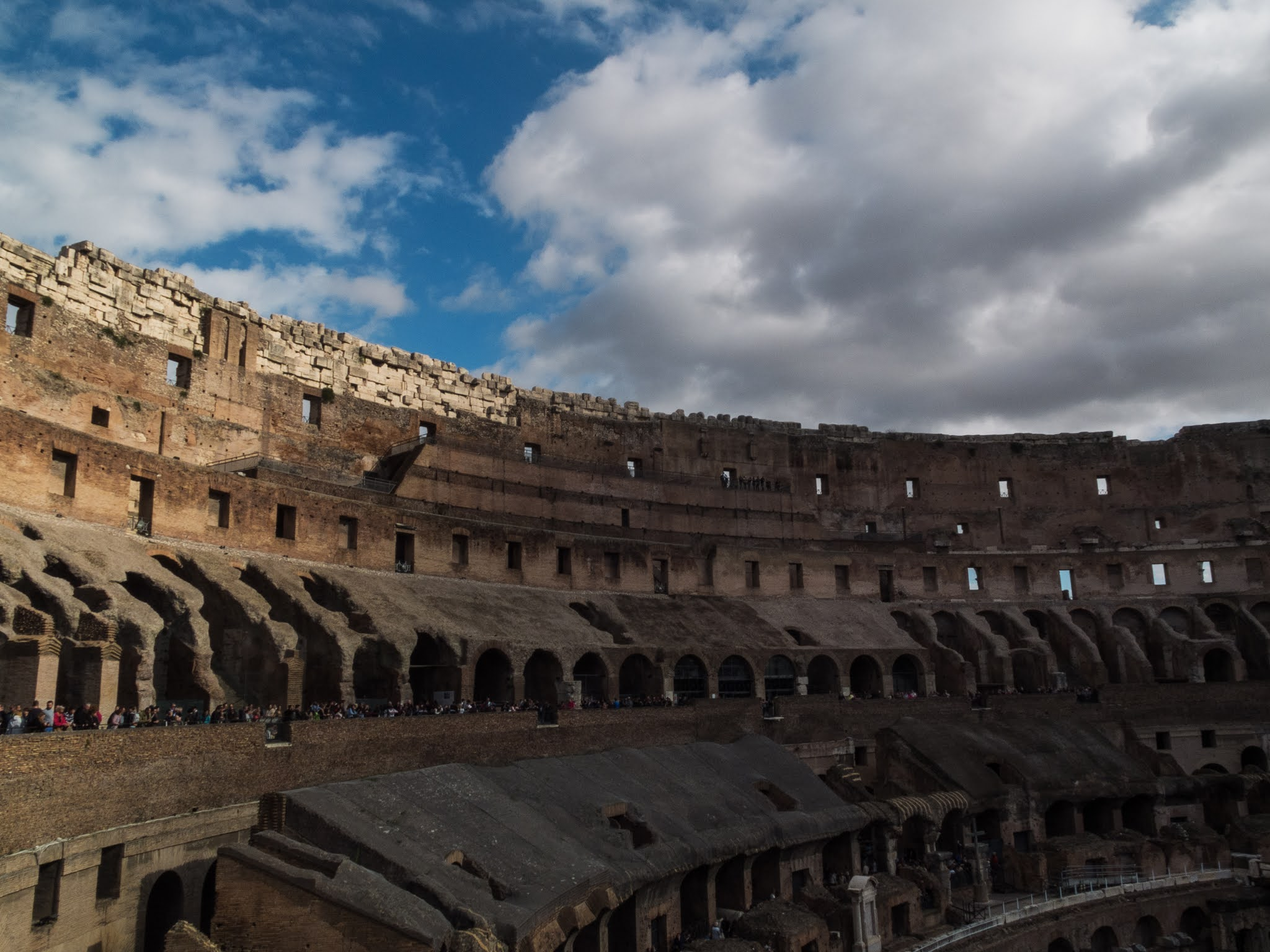View of the inside of the Colosseum with a blue and cloudy sky above.
