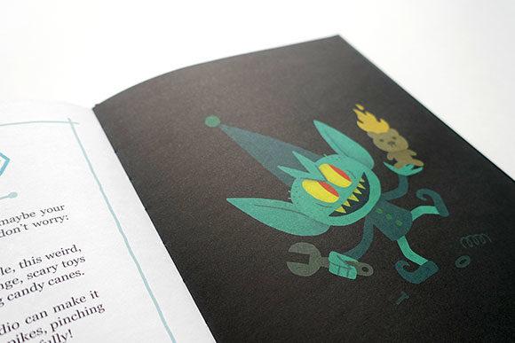 Foto de Um Livro Infantil dos Demônios, mostrando uma página com um ser que parece um duende, ou elfo, com uma expressão maligna segurando um urso pegando fogo, representado algo relativo ao mal.