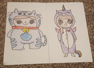 Hand Drawn Postcards, a boy in a cat onesie and a girl in a unicorn onesie