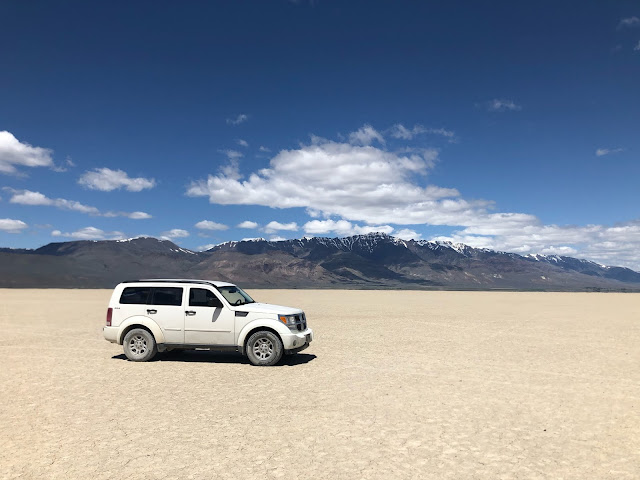 white SUV in a desert with mountains in the background