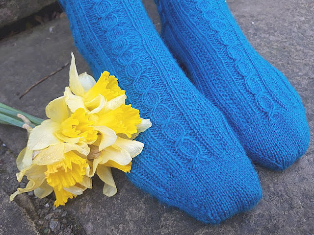 Photo shows a pair of blue patterned socks next to a bunch of yellow daffodils