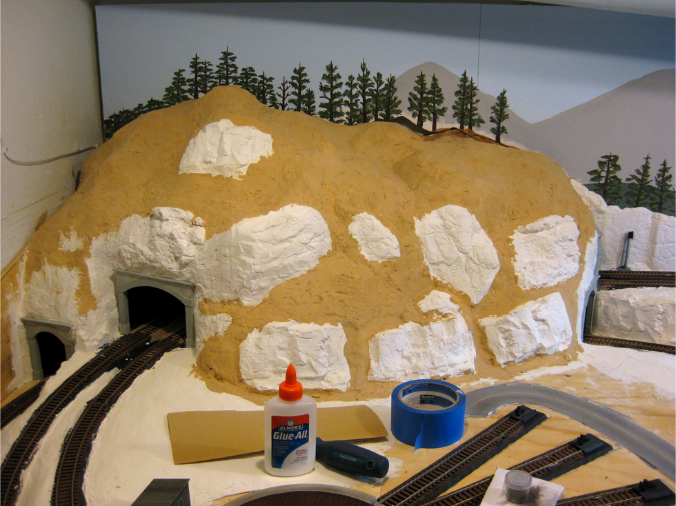 Hard shell plaster mountain terrain being painted with tan colour acrylic paint