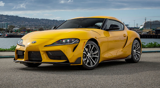 toyota supra 2021 color amarillo al lado del mar, vista lateral