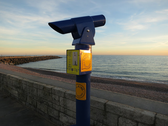 Bright blue and yellow telescope pointing out to sea with 'talking telescope' written on the side