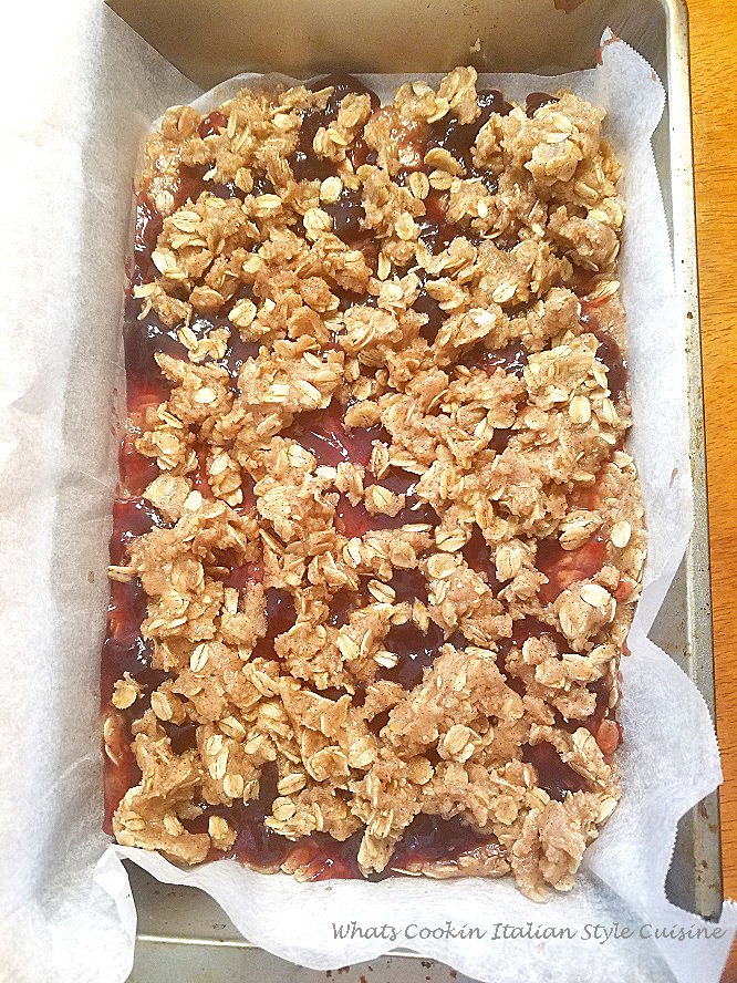 An old fashioned cookie bar filled with raspberry jam and has an oatmeal crust
