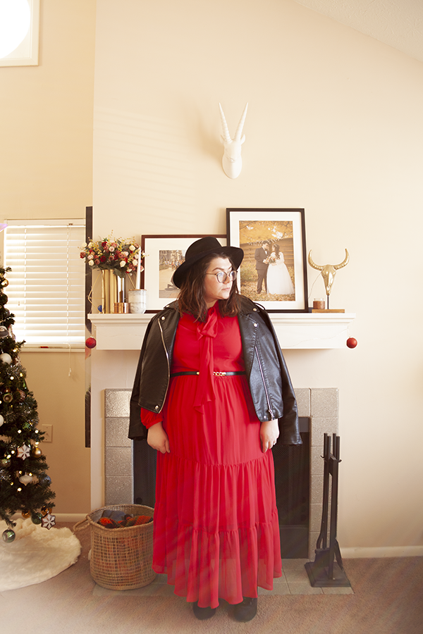 An outfit consisting of a black faux leather jacket over a red tiered maxi dress with balloon sleeves and tie neck.