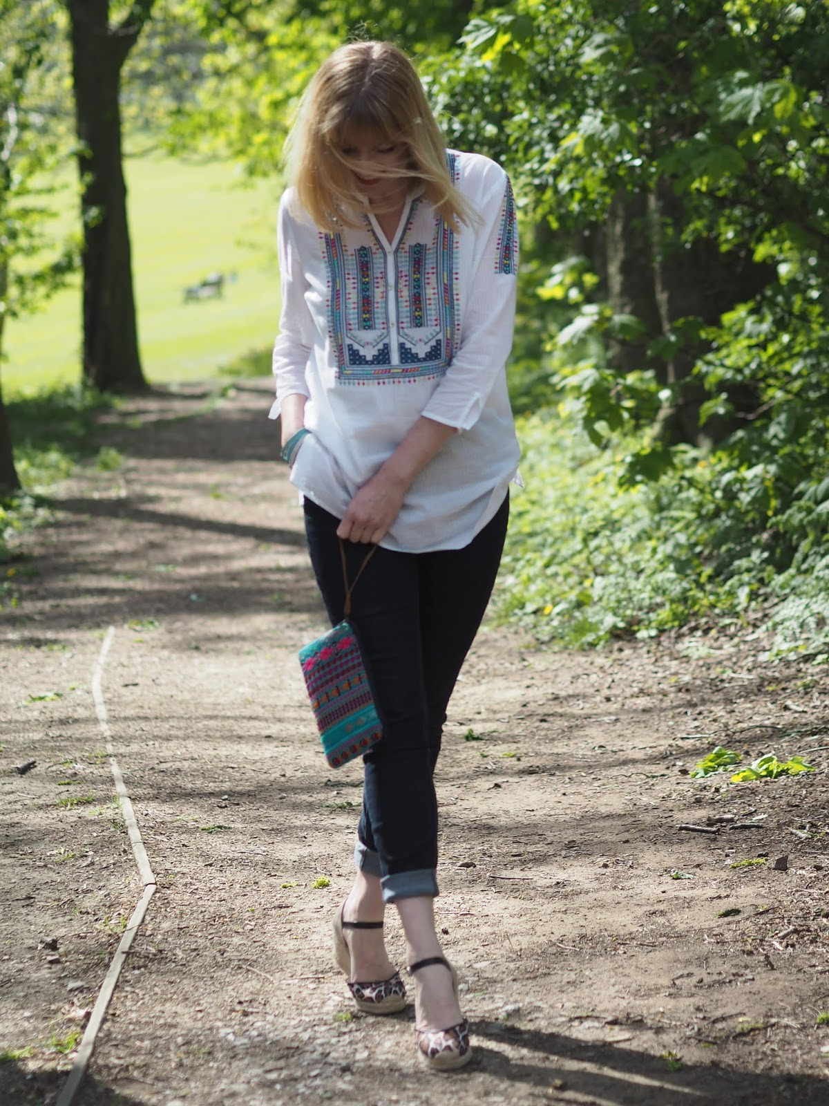 Embroidered white shirt, skinny jeans and animal print  with Aztec clutch
