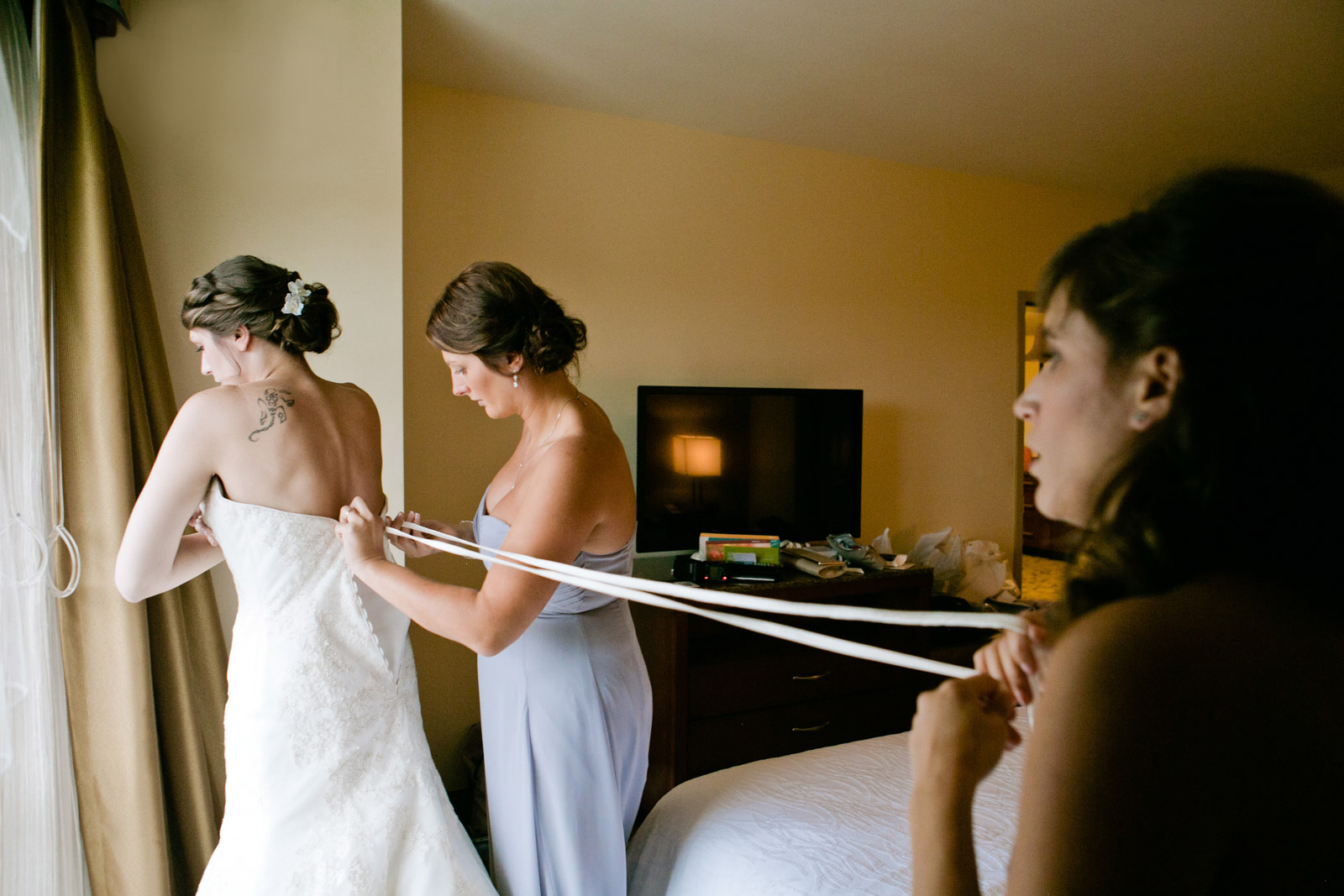 two bridesmaids help a bride get laced into her dress