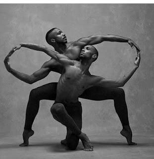 Foto de dois bailarinos negros, peito e pés desnudos , usam apenas uma meia calça preta de malha. Ambos de frente para a câmera, um está com o joelho esquerdo apoiado no chão, a outra perna inclinada na transversal  à frente e à direita; com apenas os artelhos tocando o chão. O corpo inclinado levemente à direita, braços abertos, o direito, estendido ao alto e o outro, em L, a cabeça, acompanha a inclinação do corpo, em direção ao alto e à esquerda. O outro bailarino, está posicionado atrás, curvatura do corpo à esquerda, cabeça à direita, braços em curvatura, tocando as pontas dos dedos, nos dedos do outro bailarino, finalizando com o símbolo do infinito: um oito horizontalizado. As pernas bem abertas em L invertido, mantem o equilíbrio apenas pelos artelhos no chão.