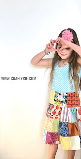 A girl showing the heart sign whilst wearing her patchwork dress.