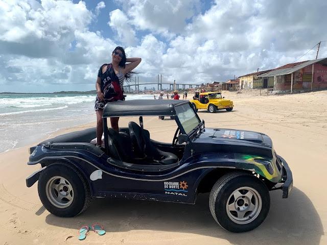 mulher em cima de um buggy na praia