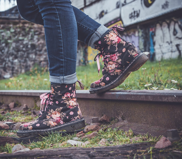 Lower shot of a woman's walking a track wearing flower printed boots