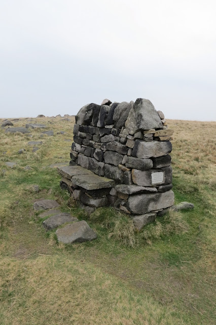 A memorial bench on the moor, built like a dry stone wall with two flat stones halfway up laid to form a seat.