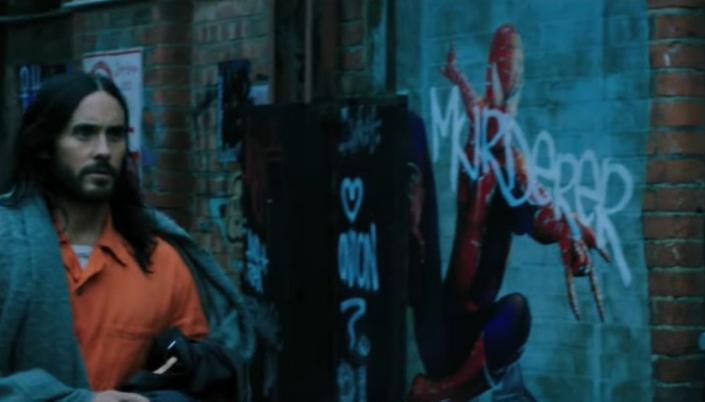 Imagem: o personagem Morbius, interpretado por Jared Leto em um macacão laranja de presidiário, passando por um rua com vários cartazes rasgados e grafitados e num deles temos uma ilustração do Homem-Aranha, com uma grafitti branca dizendo Murderer, ou seja, assassino, por cima.