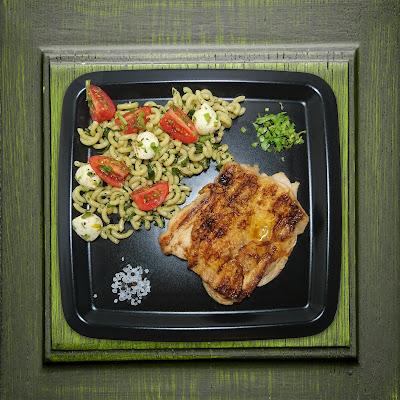 Auf einem schwarzen, viereckigen Teller liegt ein gegrilltes Hähnchensteak. Dazu wird Nudelsalat aus Gobetti gereicht. Der Nudelsalat ist mit Cocktailtomaten und Minimozarella angereichert und mit gehacktem Rucola und Kürbiskernöl vermengt.