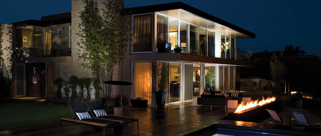Picture of modern mansion at night with outdoor fireplace on the terrace