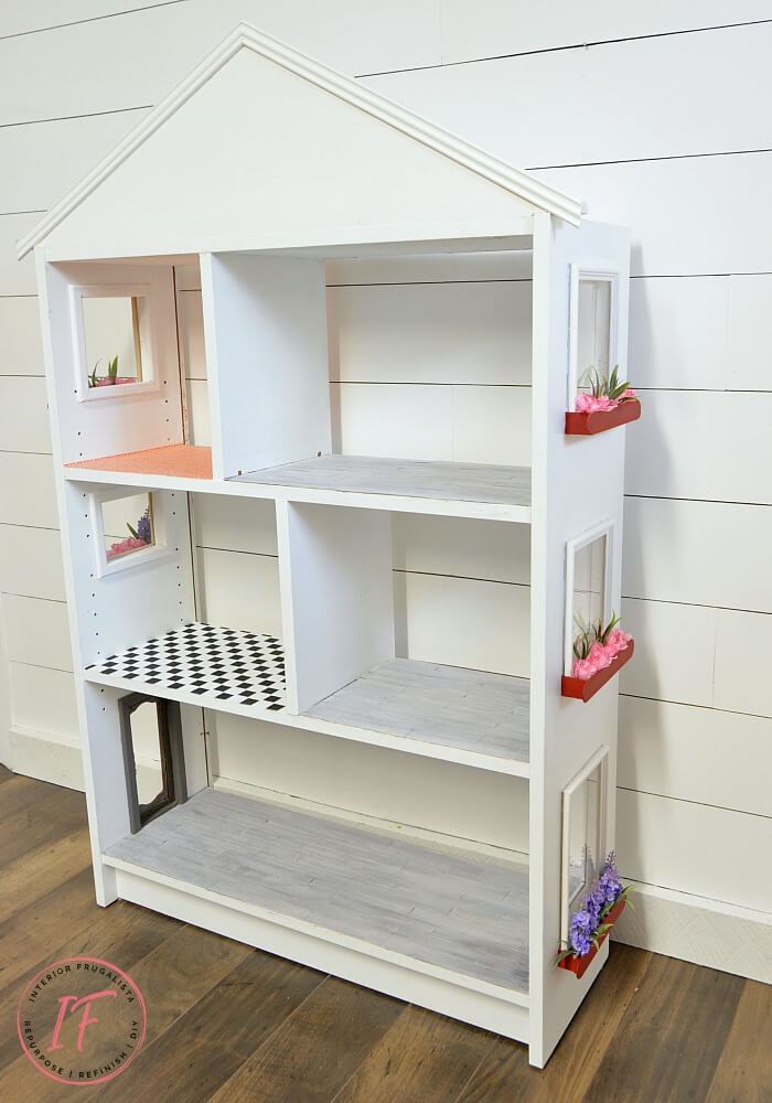 Turn an IKEA Billy Bookcase into a charming dollhouse with plexiglass windows, adorable window boxes, and a repurposed jewelry box chest front door.