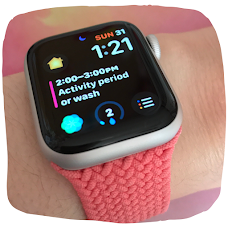 Photo of an Apple Watch. The strap is pink braided. On the digital watch face is the time, date, a calendar event and app symbols.