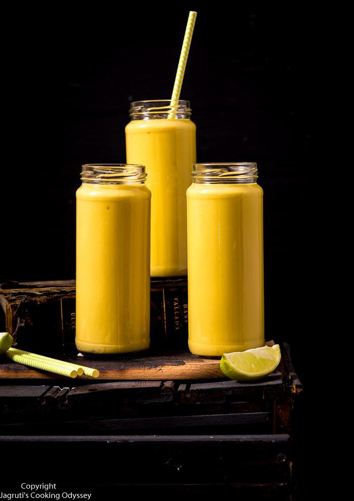 Delicious Indian mango lassi served in a bottle with paper straw and placed on a old book.