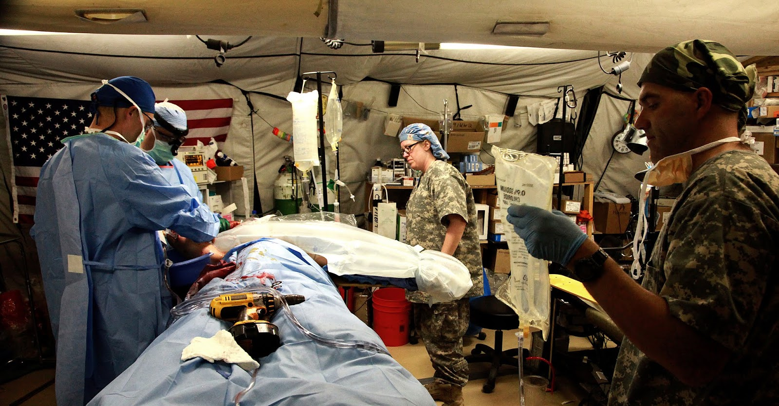 Medical personeel, some in scrubs, some in military fatigues, in a field operating room