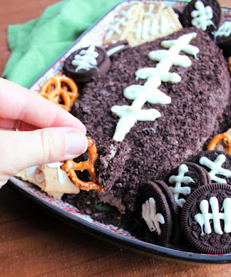 dipping pretzels into chocolate cheese ball