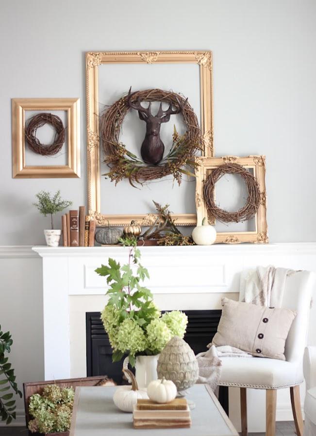 Chimenea decorada con marcos dorados y coronas de ramas secas