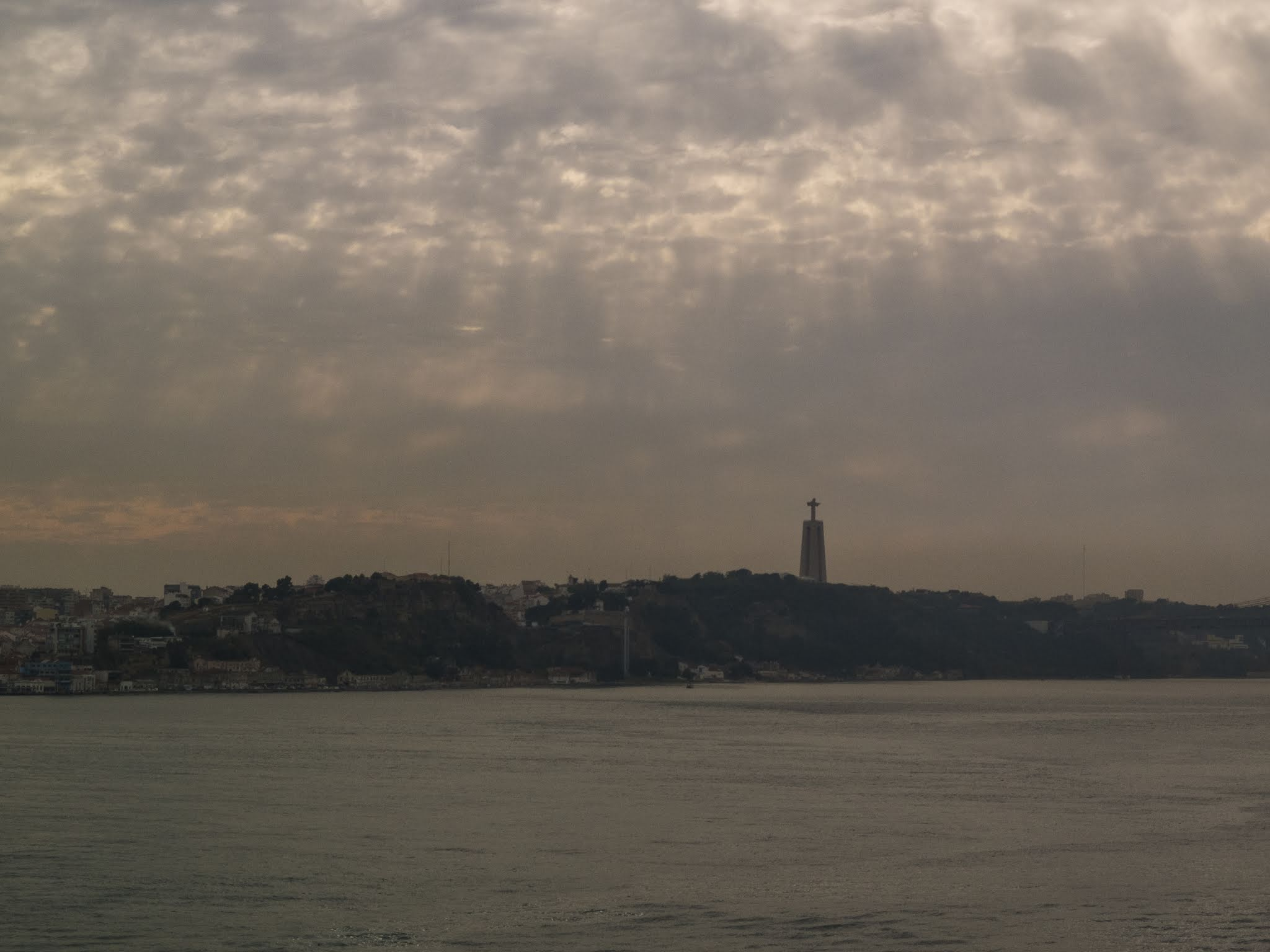 Sun shining through the clouds over the river Tagus in the port of Lisbon.