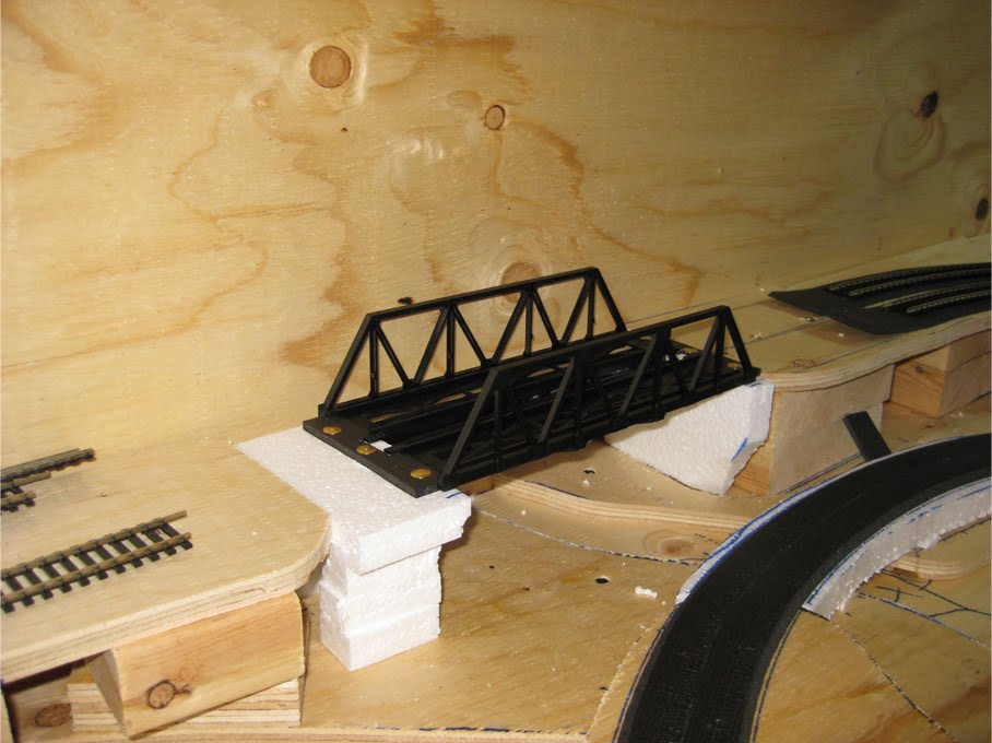 A constructed plastic Warren truss bridge kit temporarily installed between expanded foam supports