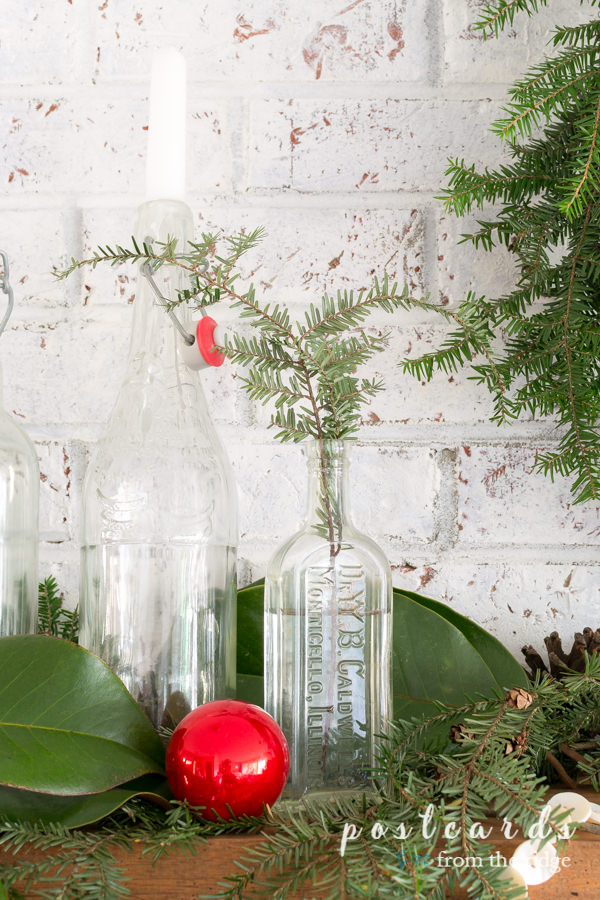 glass bottles used as a vase for hemlock branch, red glass ornament