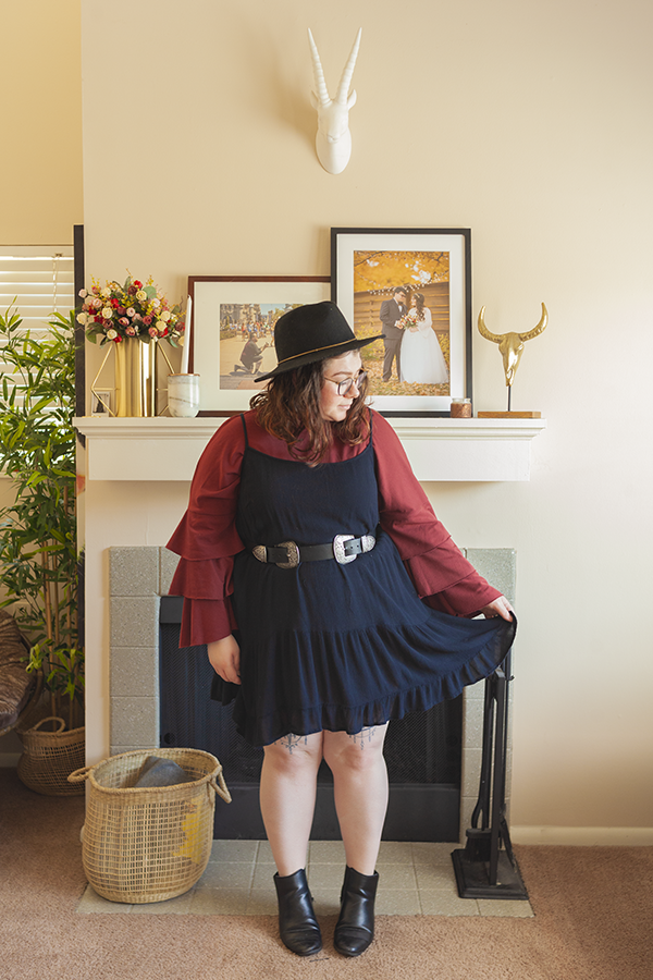 An outfit consisting of black wide brim fedora, a rust red three tiered sleeve blouse under a thin sleeve black tiered gauze dress, belted at the waist with a double buckle belt and black chelsea boots.