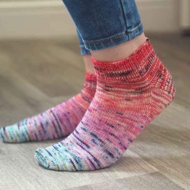 pair of short socks on feet that are faded from blue to pink