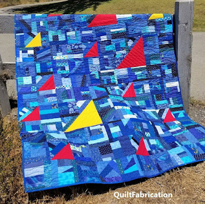 blue scrap quilt with yellow and red triangles for sails