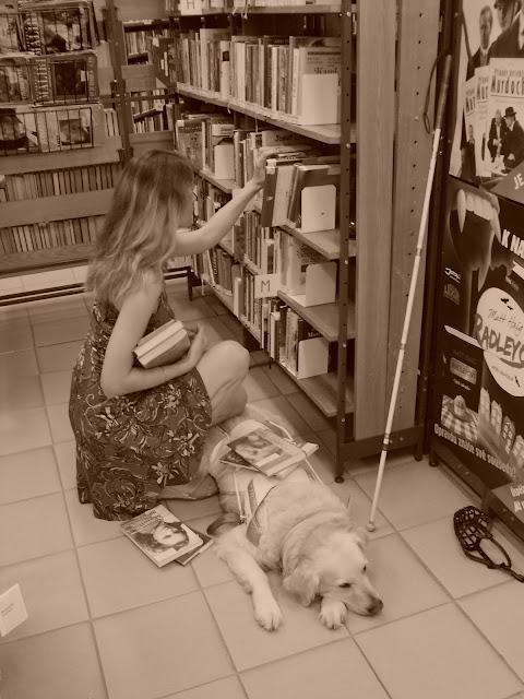 Linda sedí na bobku a vybírá knihy v knihovně v regálu. Cilka leží u nohou...