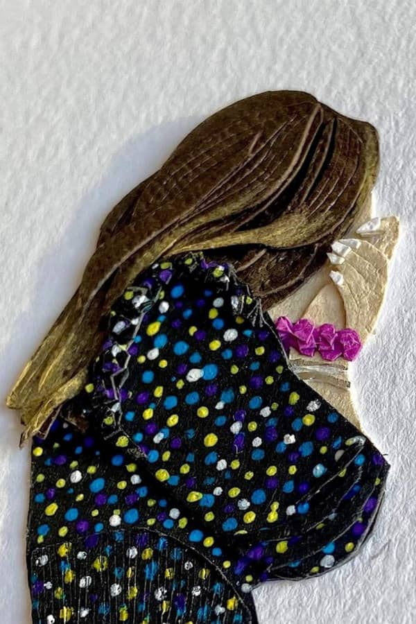 paper art detail of woman holding hands over mouth in surprise