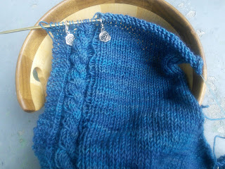 A sweater on a circular needle, knit in deep blue yarn. One side of the knitting is garter stitch and a simple cable, and then the rest is in stocking stitch.  On either side of the cable are two stitch markers with silver rose charms.