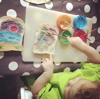 child painting bread with edible yoghurt paint
