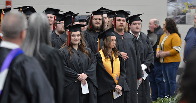 Students in their caps and gowns stand at a commencement ceremony
