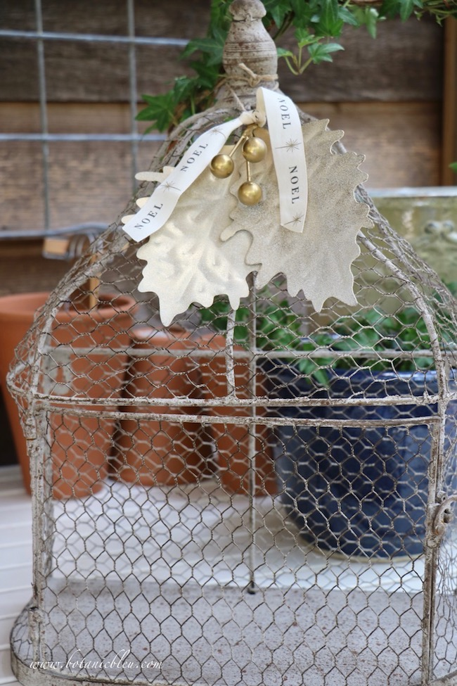 add Christmas decor with a made over gold berry leaves ornament atop a wire birdcage looks wonderful on a potting bench