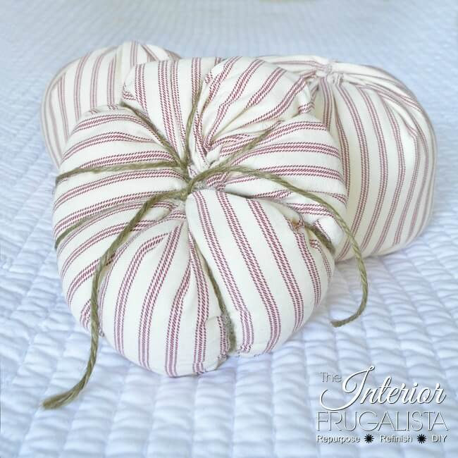 Here I show you how to salvage an old ticking stripe slipcover and kitchen cabinet knobs into pretty fabric pumpkins with farmhouse style for fall.