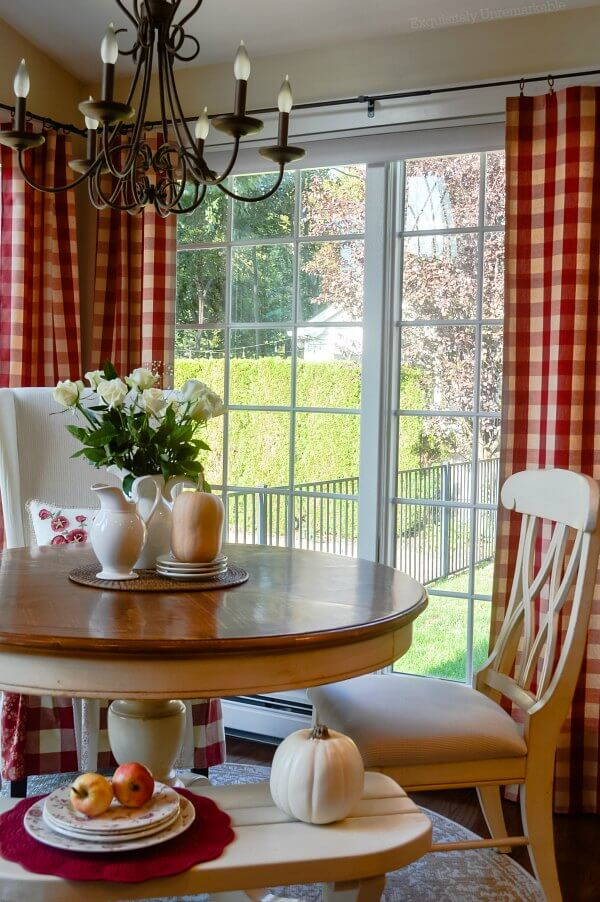 Red checked curtain panels hanging in kitchen nook around round table and chairs